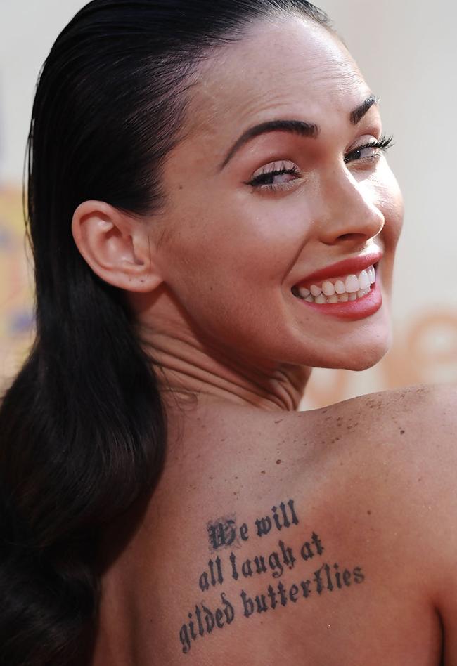 """Меган Фокс Звездата от Transformers има няколко татуировки, преди да се сдобие с тази (въпреки че се оттърва от образа на Мерилин Монро, който красеше вътрешната част на дясната ѝ ръка, за да """"не привлича лоша енергия"""")… Но една от най-видните татуси по тялото на актрисата е този в горната дясна част на гърба - три реда, адаптация от трагедията на Шекспир - King Lear, които гласят: """"We will all laugh at gilded butterflies"""". Актрисата споделя, че това има за цел да напомня """"да не се главозамайваме прекалено много по Hollywood, защото хората накрая може да ни се присмиват""""."""