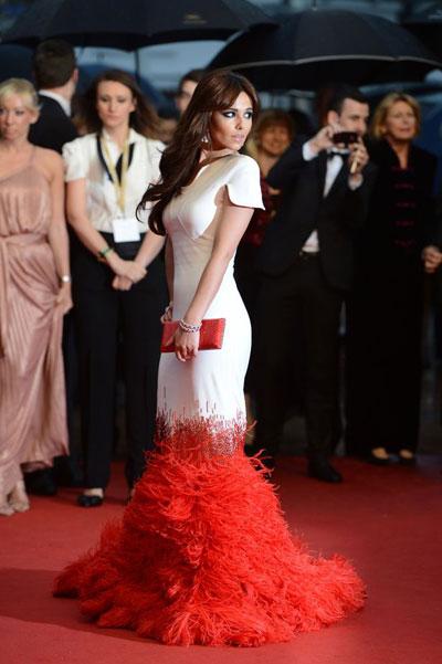 Черил Коул се сля с червения килим облечена в зашеметяваща бяла рокля с дълъг шлейф от червени пера на Stephane Rolland