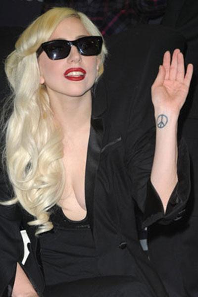 Най-старата и обичана татуировка от Лейди Гага се намира на лявата й китка и представлява знак на мира, направен в памет и чест на любимеца й Джон Ленън.