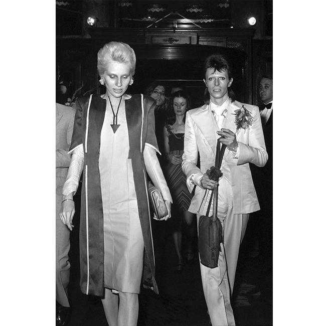 """4 юли 1973 г.  С тогавашната си съпруга - модел, актриса и музикант - Анджи Бауи. Папараците ги хващат на отиването на партито по случай пенсионирането на Дейвид. Всички тогава смятат, че той ще се оттегли от сцената, но както винаги непредсказуемият ексцентрик ги изненадва: на събитието той казва """"сбогом"""", но само на сценичната си персона - Зиги Стардъст. На същото събитие присъстват личности като Мик Джагър, Пол Макартни и Лу Рийд."""