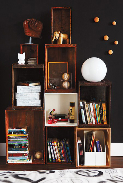 Черната стена за някои може да е твърде смело решение, но когато е само една и в много светла стая, носи артистичен дух. Точно затова шкафът за книги е направен от старите дървени щайги. themarionhousebook.com