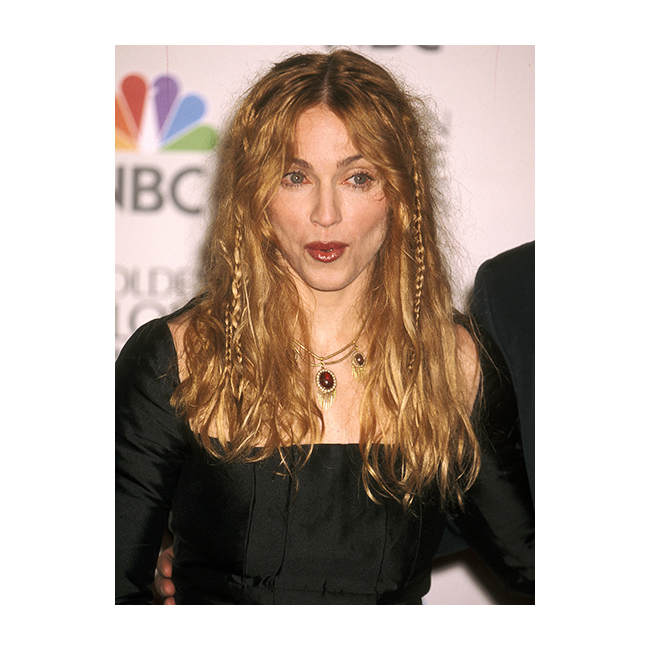 Луди плитки за акцент Бохо косата е сред запазените марки на 90-те, но тук тя не включва носенето на гигантски цветен венец. Разположените произволно плитки са един от начините да покажете, че си живеете безгрижен живот. нагледен пример е Мадона, кяото носи косата си свободна с път по средата и с няколко весели плитки за разкош.