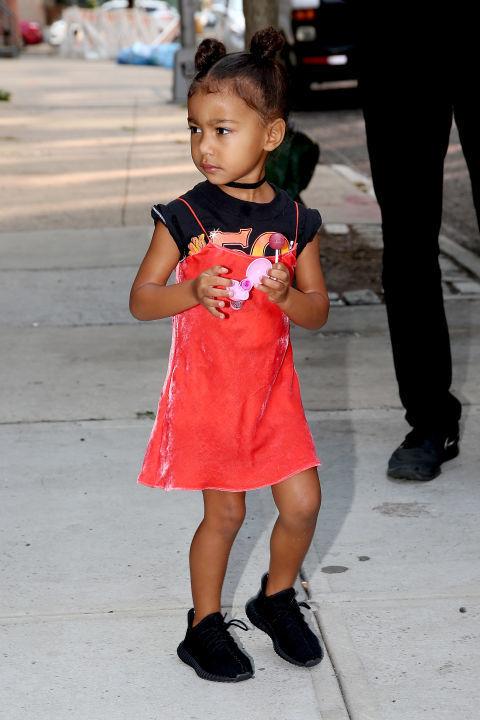Малката Норти е фен на slip роклите - тук в червено кадифе в комбо с черна тениска с надпис и разбира се бейби вариант на Yeezy кецове.