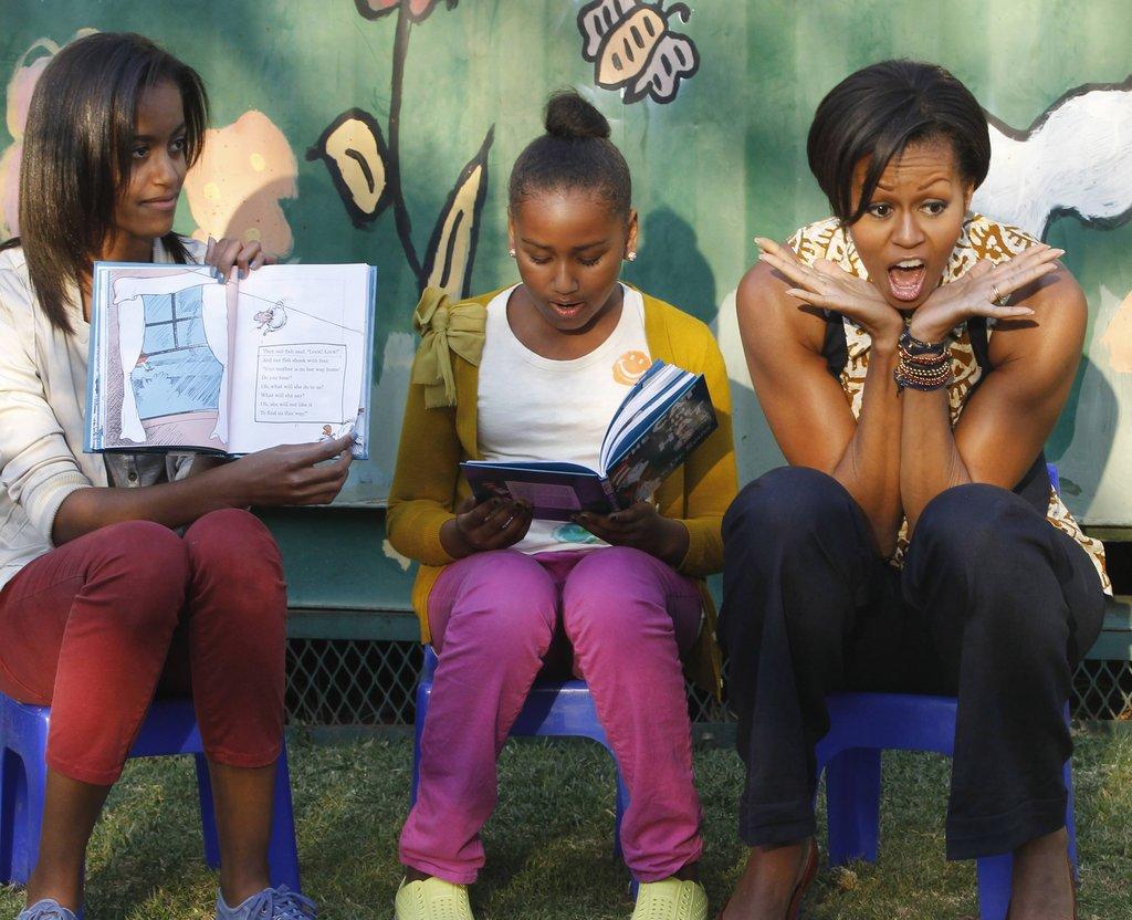 Лятото на 2011г. - Малия, Саша и Мишел четата The Cat in the Hat на дечица в Южна Африка.