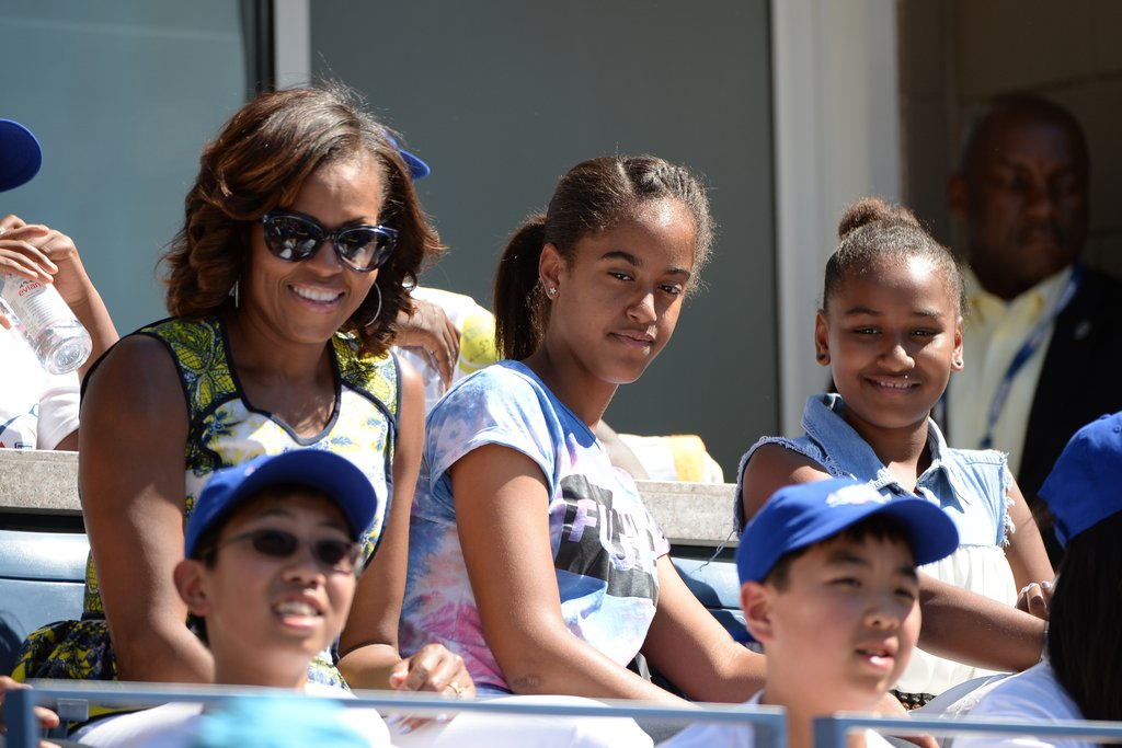 Лятото на 2013г. момичетата на Обама се наслаждават на тенис мач.
