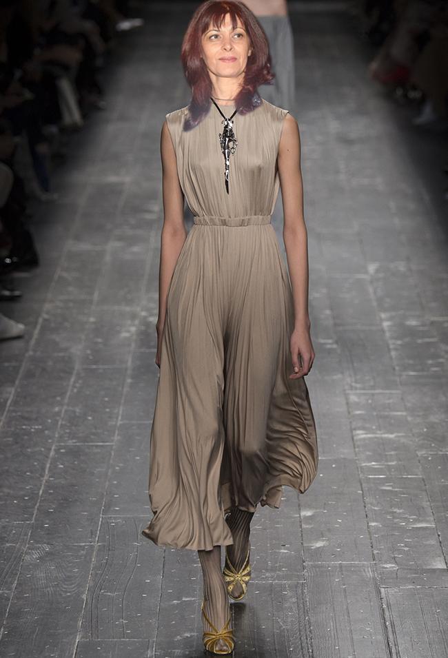 Valentino За по-официални поводи, една подобна рокля би сътворила чудеса с визията на госпожа Генчева. Кройката е доста романтична, но пък деколтето е напълно затворено, което в нейния случай е препоръчително, за да не изглежда непрофесионално и дори перверзно. Нежните плисета и приглушеният бежов тон пък поддържат цялостния тон обран и ненатрапчив. Косата е задължително прибрана, а обувките не бива да са по-високи от 7-8см. заради специфичната дължина на роклята.