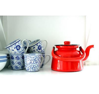 Яркият метален чайник и синьо-бялата, позната като