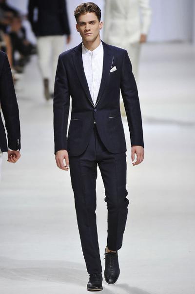 Мъжки минимализъмСако, риза, панталон. Кърпичка.Сакото е вталено, с едно единствено копче, а ризата е с малка яка и пластрон. Тук заложи на детайлите. Тънко бяло бие, с което да завършва ревера на сакото и малка бяла кърпичка в джоба, която акцентира точно минимално и на място.Ermenegildo Zegna SS2011
