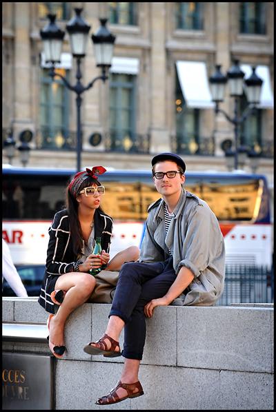 Фокусираме се върху дамата.Черното само с бели линии се комбинира чудесно с обувките в телесно, а ярко червените устни и кърпата около главатапридават нужната свежест. Харесваме и как квадратни-те рамки на очилата са съчетани с геометричните линии на сакото.(Easy Fashion)