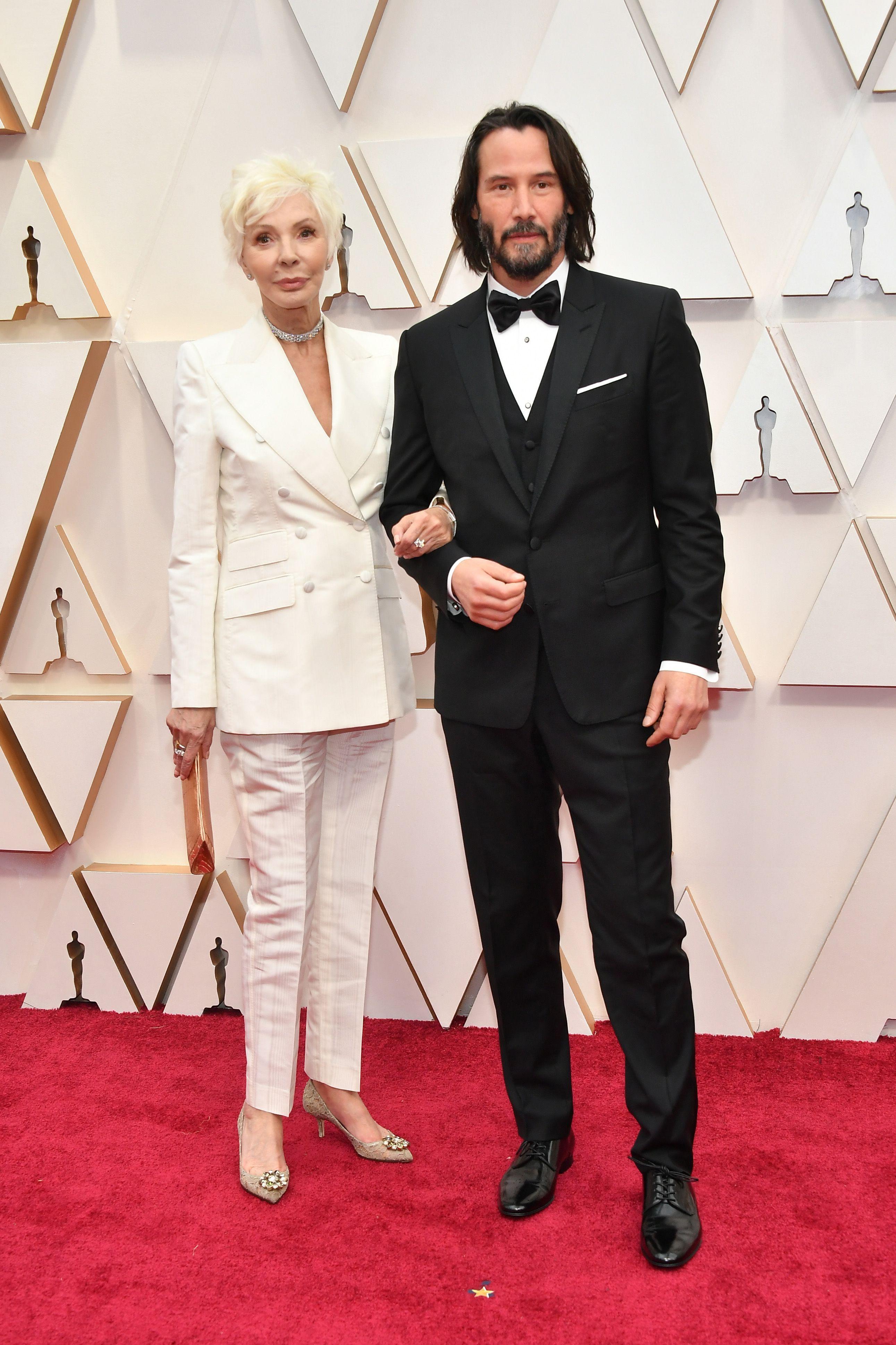Киану Рийвс с майка си  Актьорът изглежда изрядно в своя смокинг, като същото важи и за майка му. Белият костюм с двуредно сако е комплиментиран от красиви бижута и бежови обувки с кристали. Прекрасно!