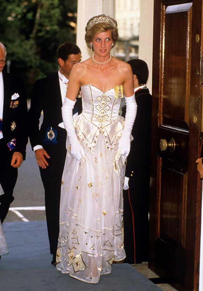 """10. Принцеса Даяна   Скандал!!! Принцесата на всички човешки сърца, Даяна, вярвате  или не, облича тази рокля не веднъж, а цели два пъти (не е толкова скандално, но, нали, в името на драмата... хаха). Роклята е дело на една от любимите дизайнерки на Ди, Catherine Walker, която има над хиляда тоалета, специално изработени за принцесата. Произведена от копринен шифон, декорирана със златни геометрични детайли, аплицирани връху нея, този """"Бял лебед от шифон"""" струва невероятните  125,000 долара."""