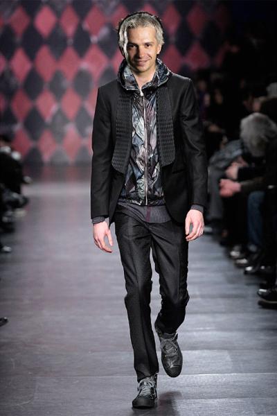 Paul Smithпролет-лято 2011 Елегантната визия на панталона и сакото се разтоварва от преливащите цветове на елека от промазана материя с качулка. За средновисок мъж със слаба фигура е много подходяща кройката на правия, леко стеснен панталон с ръб.  Тук винаги може да се заменят обувките с кецове, но не от онези скейтърските, запазена марка на Део, а по-скоро класически спортенбранд като Nike, Adidas, Puma или просто Converse.Много градско!