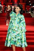 Гротескна полянка под формата на палто-рокля. Умишлено, контрастно с червения килим, изглежда много добре. Като цяло зелената флорална обвивка е адски шик заради фигурата й. Харесва ни тонирането с обувките и почти незабележимият контраст с бледо розовите обеци. Прическата отговаря като обем в баланс с аутфита. Грим - безупречен.