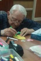 92- годишен мъж, който прави картичка за 72-годишнината от сватбата за 93-годишната си съпруга.