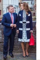 """А, фино изглежда Кралят. Толкова е """"хубава"""" тази визия, че просто не искаме да я коментираме и отдаваме внимание на клиширания мъжкарски ансамбъл. Значи откъде тази рокля с това палто? На всичко отгоре и този ярко червен сак и металически сребърни обувки. Нещо трябва да се изхвърли, но, страхуваме се, кралицата ще остане само по палто."""